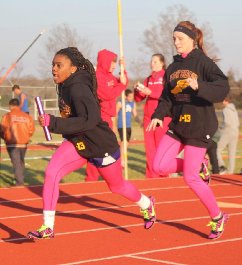 Junior+Lauren+Helmcamp+hands+off+to+freshman+Jordan+Jenkins+during+a+relay+race.