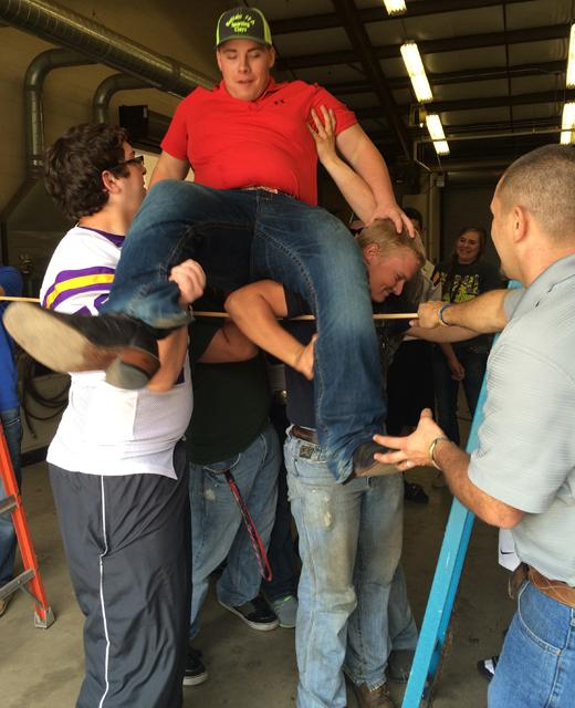 FFA students Christopher Yates and Shane Nelson lift senior Ben Reeder up and over the goal while adviser Henry Goff makes sure everyone stays safe. The group also had a team-building day at the beginning of the school year called Battle of the Gavel.
