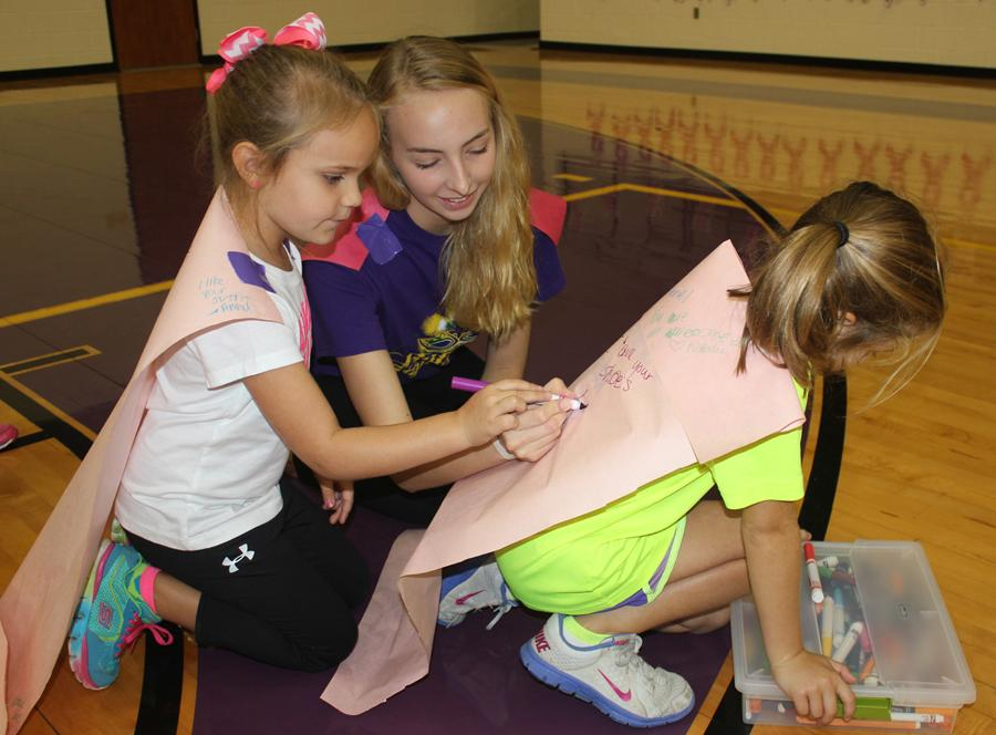 Bison Belle Josefine Poels helps two camp-goers with their capes. The children wrote kind things about one another on their capes.