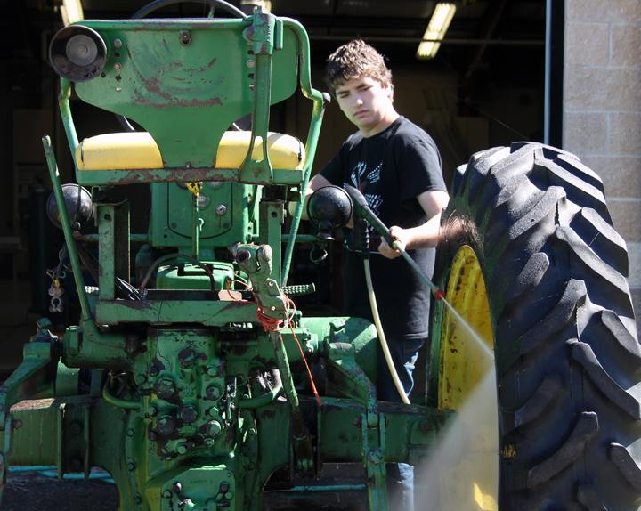 Sophomore+Steven+Millar+works+on+pressure+washing+the+tractor+that+his+ag+class+is+restoring.