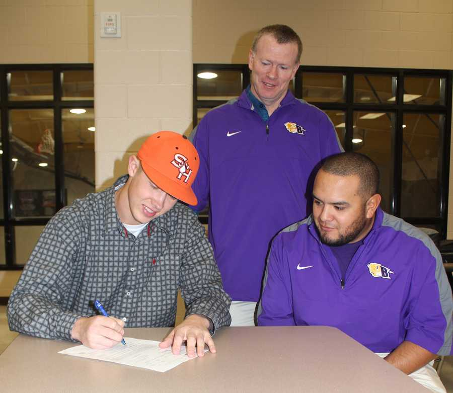 Senior+Kyrell+Miller+signs+with+SHSU+while+athletic+director+Gary+Grubbs+and+coach+Ray+Ramos+look+on.