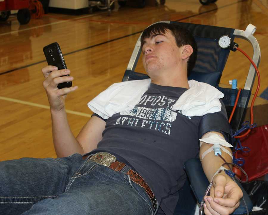 Junior+Trey+Minter+relaxes+with+his+cell+phone+while+donating+blood+Friday.+The+NHS-sponsored+events+collected+69+units+for+donation.