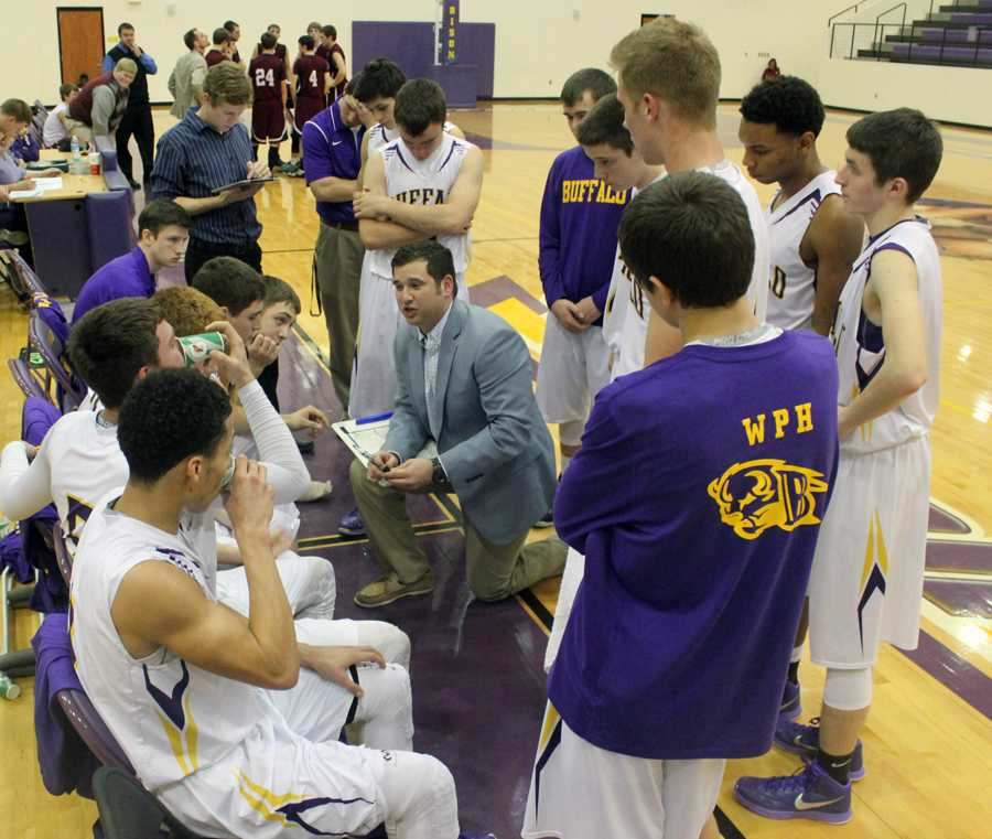 Coach Welch talks with his team between quarters.