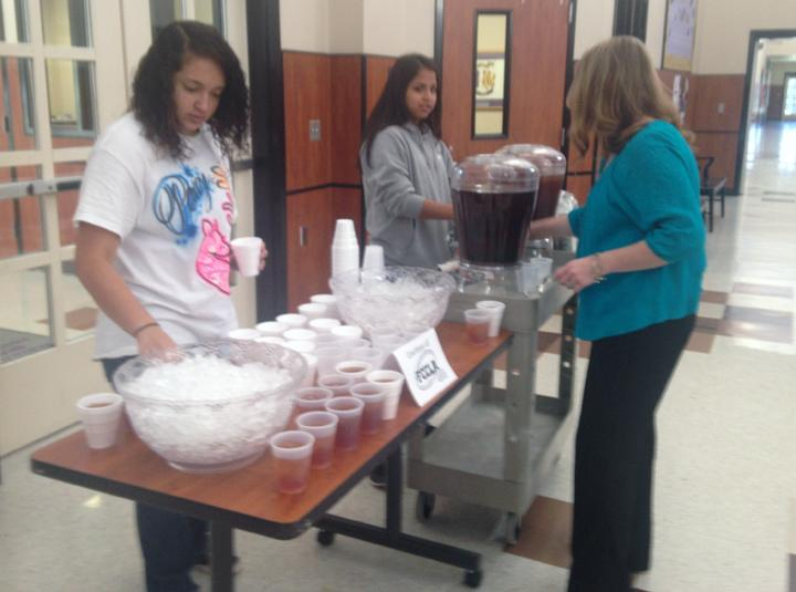 FCCLA+sponsor+Wendy+Neyland+helps+members+Victoria+Shaw+and+Annel+Escobar+set+up+tea+for+the+student+body+during+FCCLA+week.