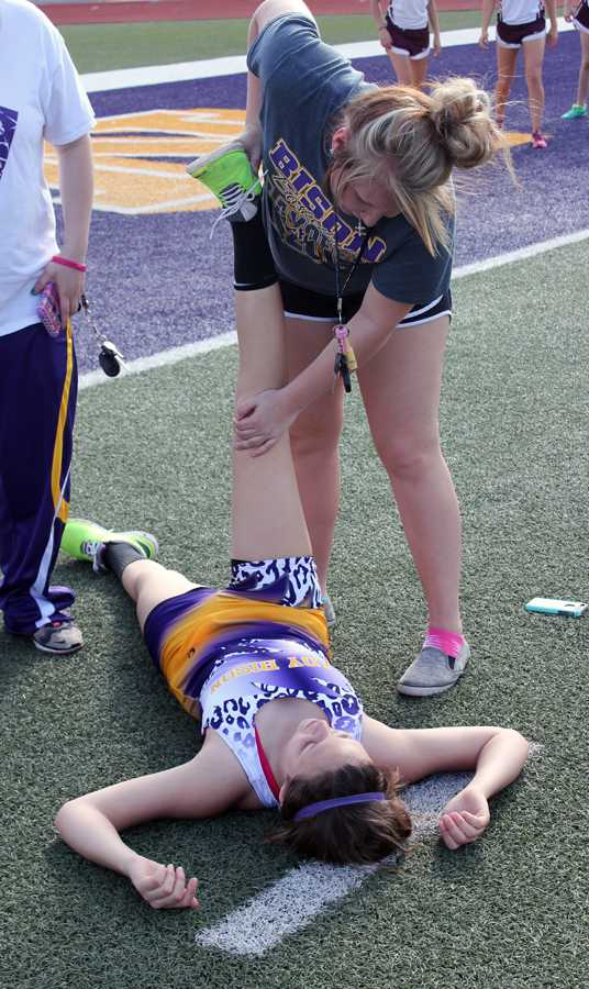 Junior Makayla Troyer helps the runners stretch before the meet.