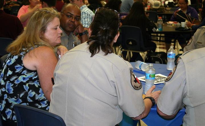 Science teacher Deborah Oehler visits with DPS officer Marvin Jenkins and members of the LCSO at a pizza lunch on Thursday.
