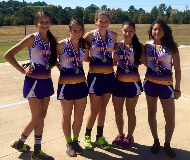 The+girls+cross+country+team+poses+with+their+medals+after+district.+They+compete+Monday+at+regionals.+
