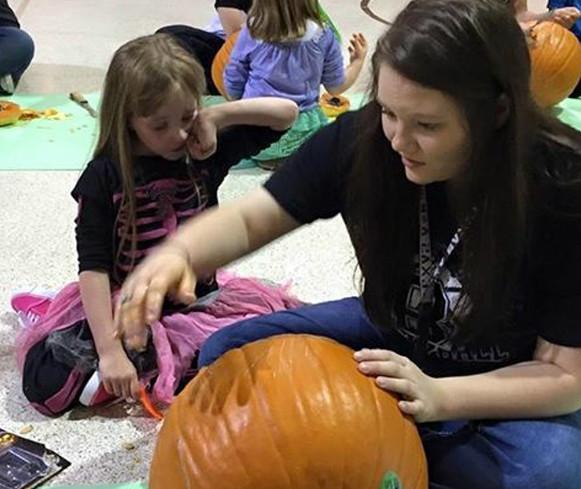 Senior+Brianna+Johnston+works+on+her+pumpkin+with+her+preschool+helper.