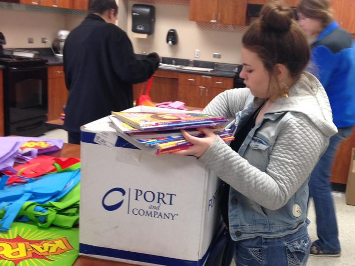 Senior+Emmelee+Weathers+sorts+through+coloring+books+while+the+Community+Service+class+fills+bags+for+the+children%27s+hospital.