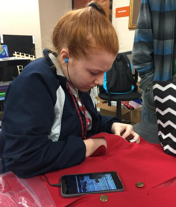 FCCLA member Jessica Devore sews her patch onto her jacket to get ready for the FCCLA Regional Convention.