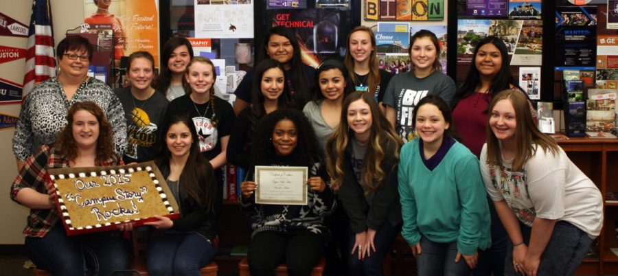 The+journalism+staff+poses+with+their+giant+cookie+cake+and+honorable+mention+certificate+from+the+Lifetouch+Yearbook+Showcase.