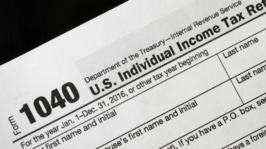 A 1040 tax form appears on display, Tuesday, Jan. 10, 2017, in New York. The IRS is delaying tax refunds for millions of low-income families as the agency steps up efforts to combat identity theft and fraud. Starting in 2017, a federal law requires the tax agency to delay refunds until Feb. 15 for people who claim the earned income tax credit and the additional child tax credit. The IRS says processing times will delay most of the refunds until the end of February. (AP Photo/Mark Lennihan)