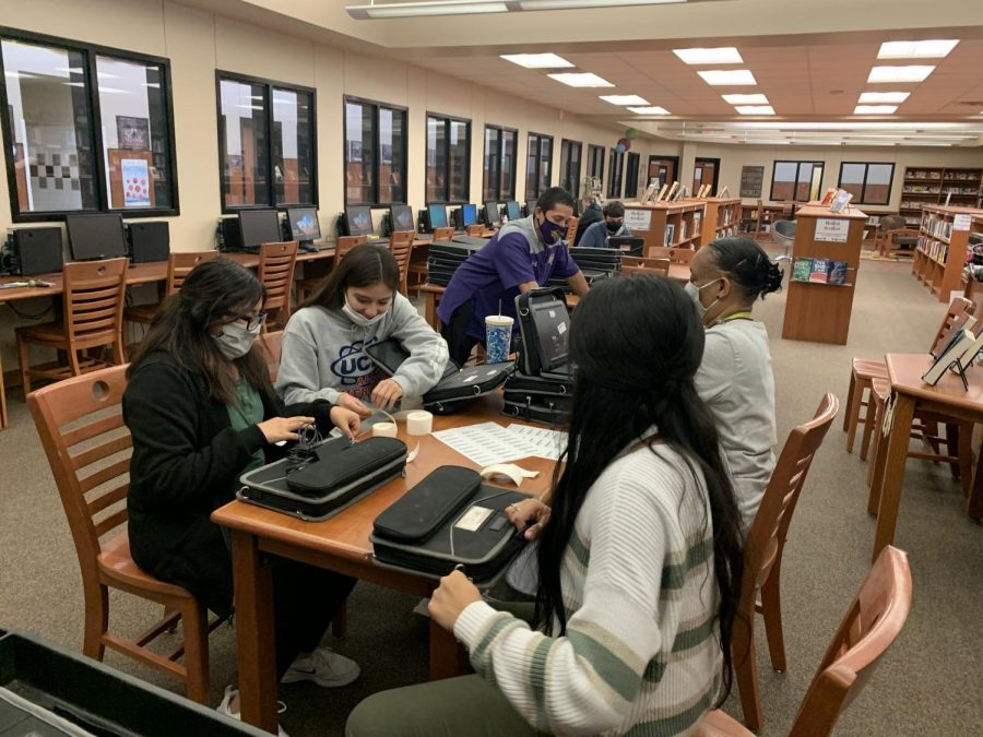 Journalism students help Assistant Principal Lu Olvera, library aide Percillar Reed and Librarian Melonie Menefee with Chromebook processing. The devices had to be barcoded before distribution.