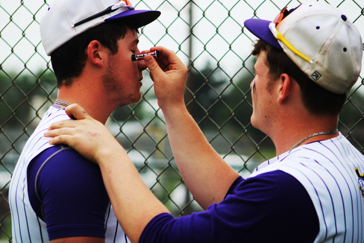 Sophomore Zayne Johnson helps senior teammate Brett Hoffman get ready for their last game of the season. The seniors, including Brett, and their parents, were honored before the game.