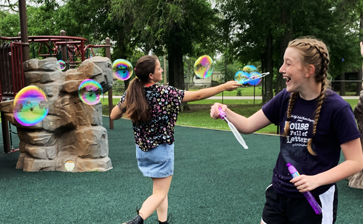 Freshmen Emma Cocking and Nicolette Arabie have a little fun with bubbles after OAP competition.