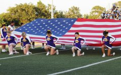 Cheerleader and Belle members showcase the American flag during the pre-game show honoring first responders.