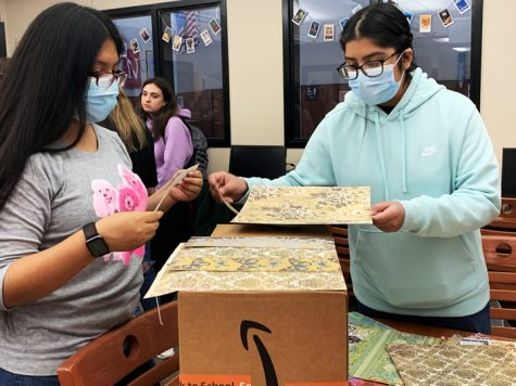 Student council members cover recycled boxes with scrapbook paper so that teachers can have decorated boxes to collect paper in for recycling.