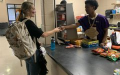 Sophomore  Aiden  Savage  waits  on  customer Caidence King at the concession stand after school. The after-school  hours have been a big hit with students on their way to the  bus.