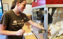 Sophomore Emma Cocking fills popcorn bags while working the concession stand during a JV football game.
